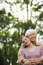 Happy grandmother and granddaughter embracing in park portrait of senior women from behind Royalty Free Stock Photos