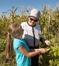 Happy grandmother with granddaughter holding cucumber harvest in the garden Stock Photo
