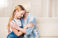 Happy grandmother and granddaughter sitting on sofa and hugging Royalty Free Stock Photo