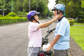 Happy grandmother help grandfather to wear a helmet on road Stock Photo