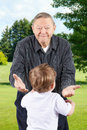 Happy grandpa with open arms senior men or grand father bending down to welcome grand kids Royalty Free Stock Image