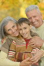 Happy grandparents with grandson smiling their in autumn forest Stock Photography