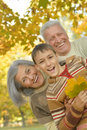 Happy grandparents with grandson smiling their in autumn forest Royalty Free Stock Photography