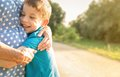 Happy grandson hugging to his grandmother outdoors portrait of over a nature outdoor background Stock Photo