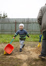 Happy grandson runs with grandfather toy cart at the countryside Stock Image