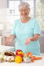 Happy granny preparing healthy food grandmother showing raw materials on kitchen counter smiling looking at camera Royalty Free Stock Photos