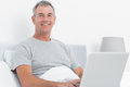 Happy grey haired man using his laptop in bed smiling at camera bedroom at home Stock Photo