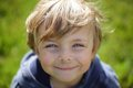 Happy grimy kid against green blurred natural background Stock Photography