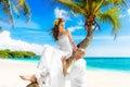 Happy groom and bride having fun on the sandy tropical beach und under palm tree wedding honeymoon concept Royalty Free Stock Image