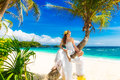 Happy groom and bride having fun on the sandy tropical beach und under palm tree wedding honeymoon concept Stock Photo