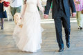 Happy groom and bride walk on road Royalty Free Stock Images