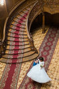 Happy groom carry his wife near big wooden stairs at old vintage house, top view Royalty Free Stock Photo