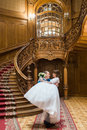 Happy groom carrying his wife with bouquet near big wooden stairs at old vintage house Royalty Free Stock Photo