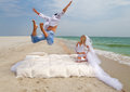 Happy groom flying bed to his bride beach Stock Photo