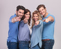 Happy group of casual people pointing fingers to the camera on grey background Royalty Free Stock Photos