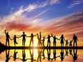 Happy group of diverse people friends family team together standing holding hands and celebrating success water reflection sunset Stock Photos