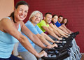 Happy group exercising on bikes Stock Photo