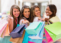 Happy group of female shoppers holding bags and smiling Stock Image
