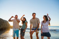 Happy group of friends dancing together on the beach Royalty Free Stock Images