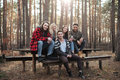 Happy group of friends sitting outdoors in the forest. Royalty Free Stock Photo