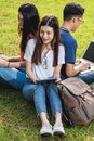 Happy group friends students sitting in park at college Royalty Free Stock Photo