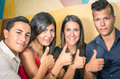 Happy group of friends with thumbs up showing Stock Image