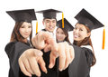 Happy group graduate students point to the same direction over white background Royalty Free Stock Photo