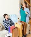 Happy guy and girl with purchases in home Stock Photos