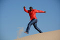 Happy guy running down dune full body of an african american young man with smiling facial expression jumping and a barefooted Stock Photography