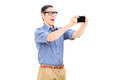 Happy guy taking a selfie with cell phone isolated on white background Stock Photo