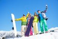 Happy guys friends men and women stand in snow with snowboards lifting and waving hands Stock Photos
