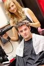 Šťastný kaderník sušenie jej zákazníci vlasy