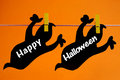 Happy halloween greeting written across black ghosts cards hanging from pegs on a line against an orange background Stock Photography