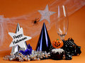 Happy halloween party decorations with cobweb and spider champagne glass hats chocolate cupcake stars and streamers on orange Royalty Free Stock Images