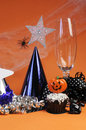 Happy halloween party decorations vertical with cobweb and spider champagne glass hats chocolate cupcake stars and streamers on Stock Photos
