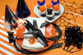 Happy halloween party table with orange polka dot plates an chocolate cupcakes with black cat pumpkin and bats decorations on Stock Image