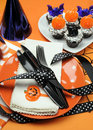 Happy halloween party table vertical with orange polka dot plates an chocolate cupcakes with black cat pumpkin and bats Stock Image