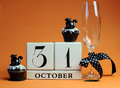 Happy halloween save the date white block calendar with champagne glass and chocolate muffins with black cat decorations and polka Royalty Free Stock Photography