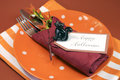 Happy halloween table place setting with orange polka dot and stripe plate and napkin black cat decoration against autumn fall Stock Photo