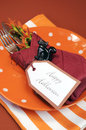 Happy halloween table place setting with orange polka dot and stripe plate and napkin vertical black cat decoration against autumn Stock Image