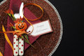 Happy halloween table place setting with red polka dot cutlery and pumpkin decorations on a black tablecloth and copy space or Stock Image