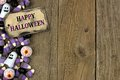 Happy Halloween tag with candy side border over aged wood