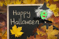 Happy halloween witch autumn message in chalk writing on a black school board on leaves background puppet made of wooden spoon Royalty Free Stock Image