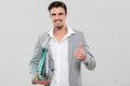Happy handsome man holding binders and showing thumbs up Royalty Free Stock Photo
