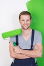 Happy handsome man painting his house in dungarees Royalty Free Stock Photos