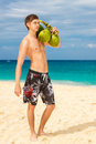 Happy handsome young male beach smiling at camera holding coconu coconuts under the sun on sunny summer day during holidays Royalty Free Stock Photography