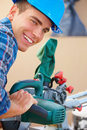 Happy handy man at work using Table saw Stock Photography