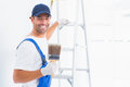 Happy handyman with paintbrush while climbing ladder portrait of at home Stock Photos