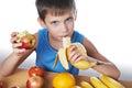 Happy healthy boy eating banana and apple isolated Royalty Free Stock Photo