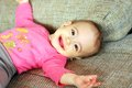 Happy healthy loved baby girl laughing nine months old on the bed Royalty Free Stock Image